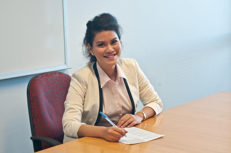 Business woman signing contract agreement in office. Asian business lawyer woman signing contract agreement in office and smile stock image