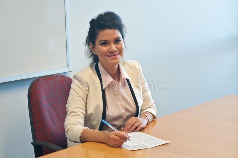 Business woman signing contract agreement in office. Asian smart business woman signing contract agreement in office and smile royalty free stock photo