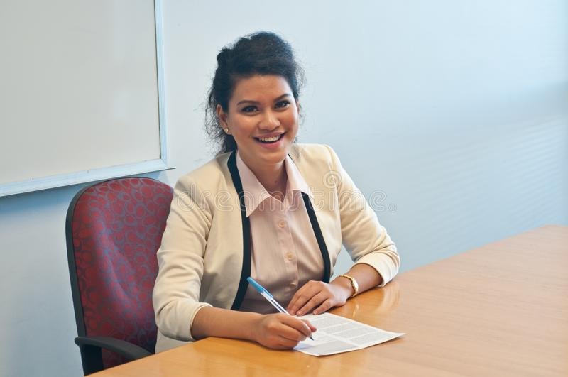 Business woman signing contract agreement in office. Business woman is signing contract agreement in office and laughing royalty free stock photo