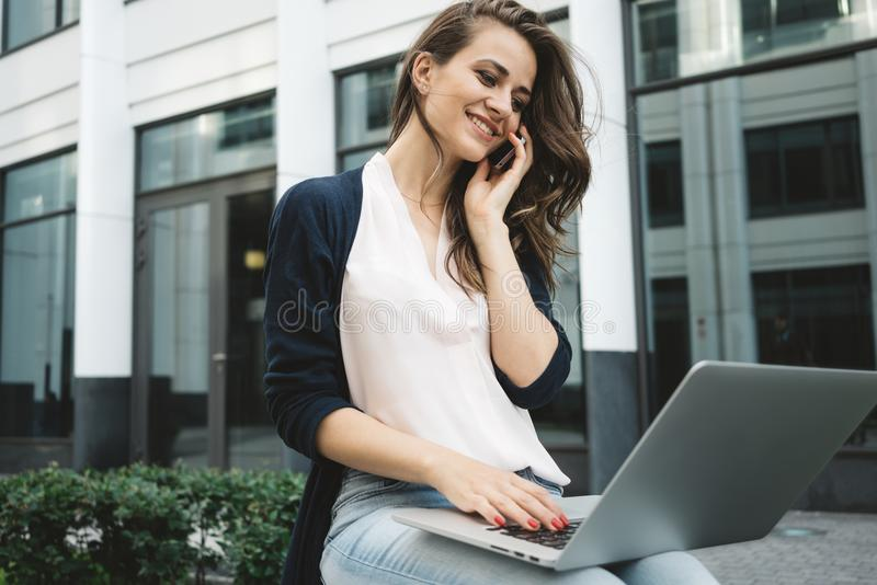 Business woman sits in urban park and typing text on modern laptop and talk by mobile phone stock photography