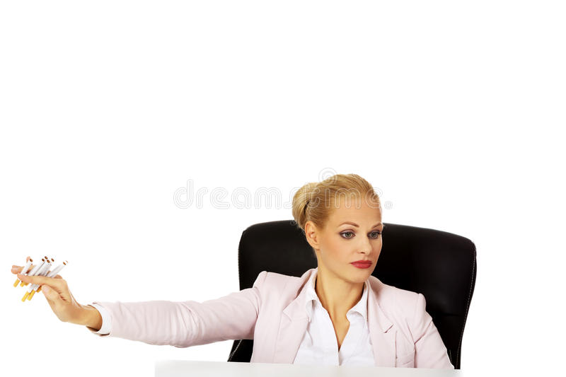 Business woman sitting behind the desk don't want to smoke.  stock image