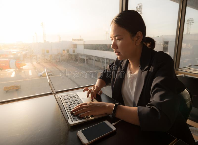 Business woman sitting at cafe and working on laptop while waiting for her flight royalty free stock image