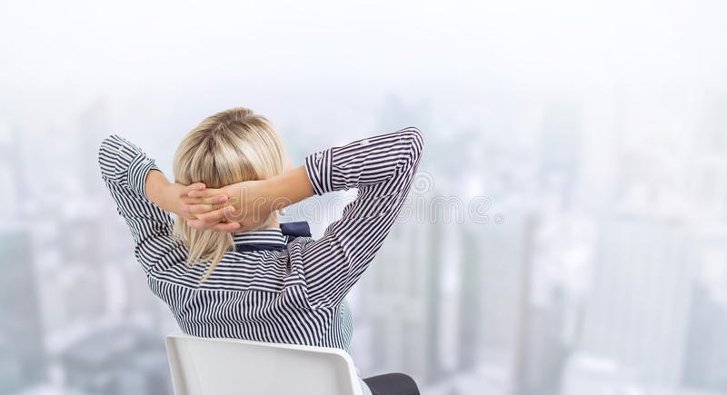 Business woman sitting in chair with city's skyline in background stock image