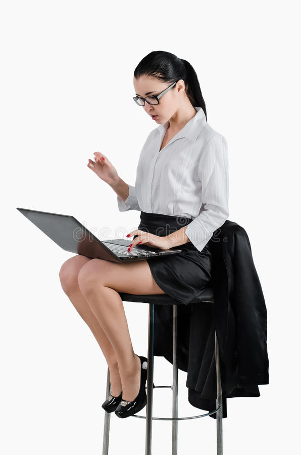 Business woman sitting on a chair and looking at a laptop. White royalty free stock images
