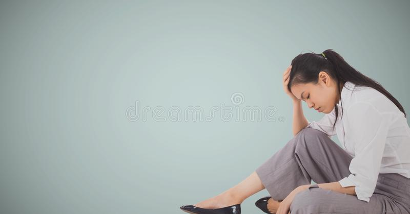 Business woman sitting with head on hand against light blue background. Digital composite of Business woman sitting with head on hand against light blue royalty free stock photos