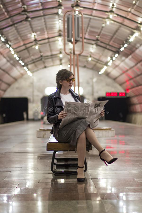 Business woman sitting reading a newspaper. Beautiful girl in a business suit and sunscreen sitting reading a newspaper stock images