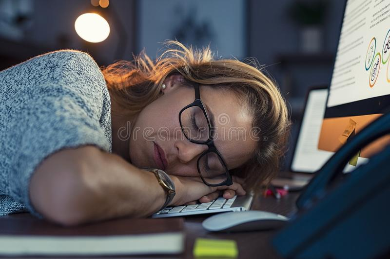 Business woman sleeping on computer at night royalty free stock photos