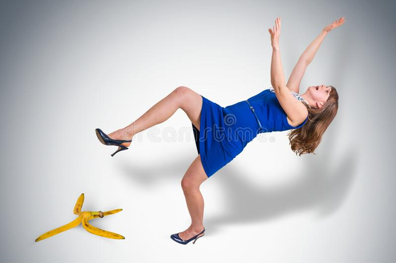 Business woman slipping and falling from a banana peel royalty free stock image