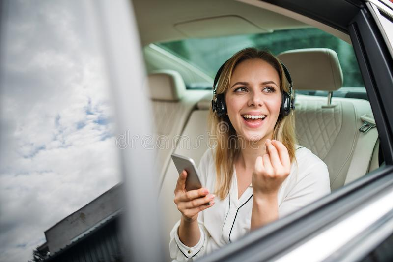 Business woman with smartphone and headphones sitting on back seats in taxi car. stock photography