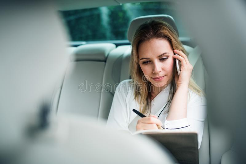 Business woman with smartphone sitting on back seats in taxi car. stock photography