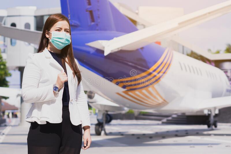 The business woman smiling and wearing protection face mask against coronavirus, PM 2.5 and cold stnding in front of airplane. Coronavirus and Air pollution pm royalty free stock images