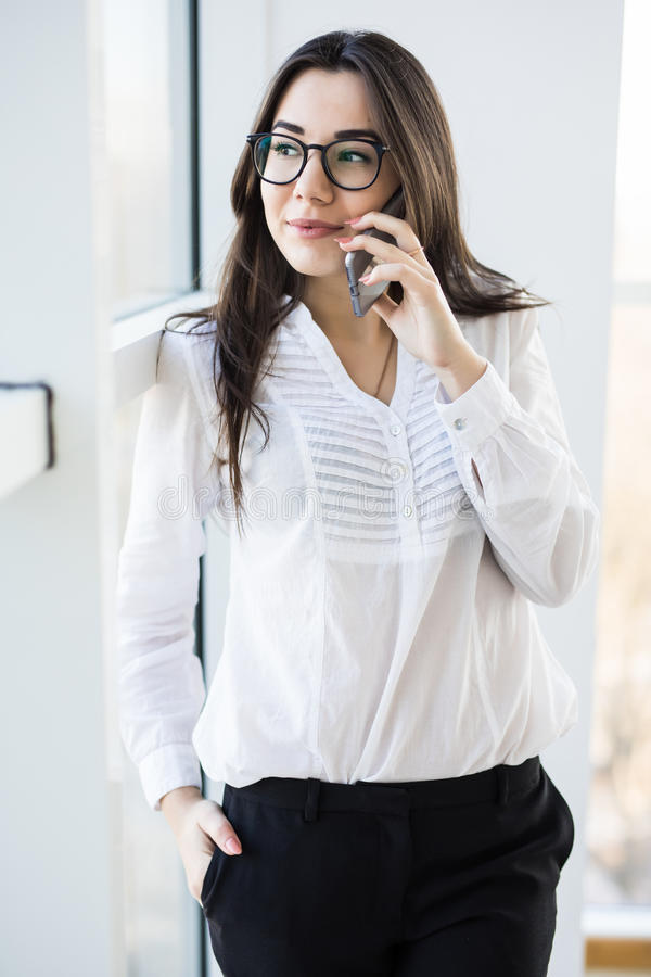 Business woman speak on phone near big office window stock image