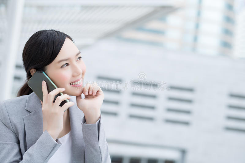 Business woman speak smart phone. Business woman smile speak smart phone in office, asian beauty stock photos
