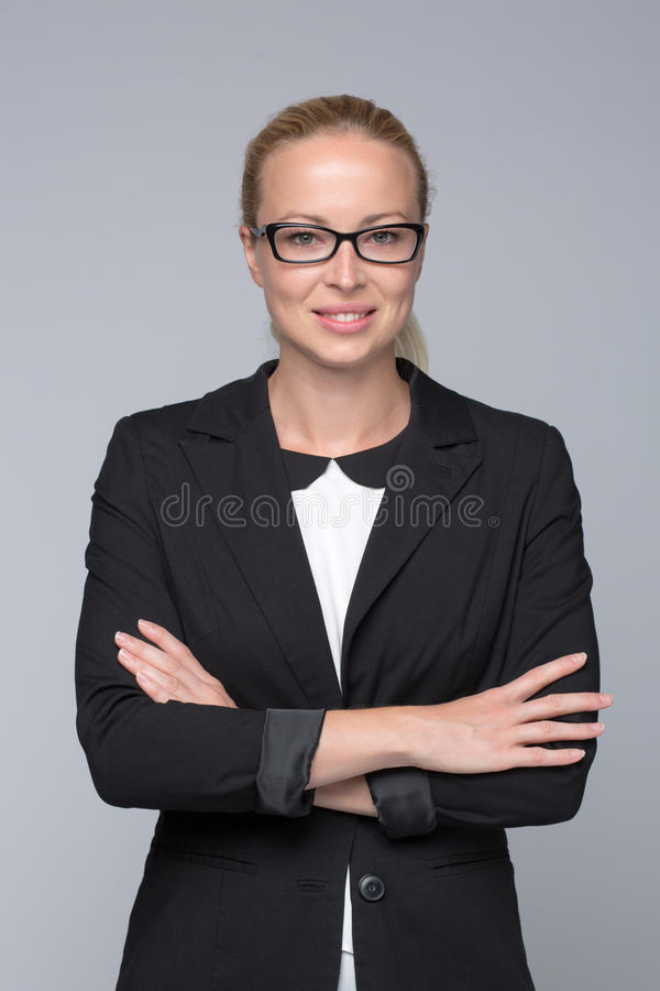 Business woman standing with arms crossed against gray background.. stock images