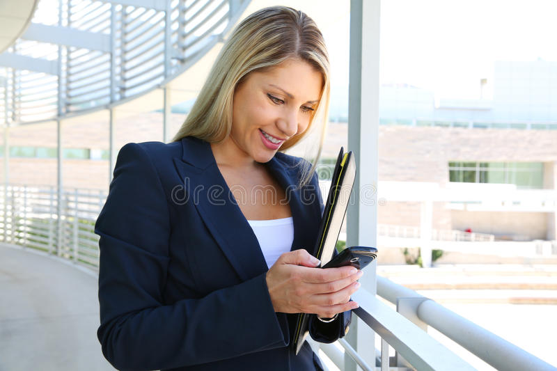Business woman standing in business building with folder and text on the phone. A beautiful businesswoman holding a folder stock photo