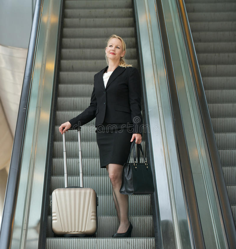 Download Business Woman Standing On Escalator With Travel Bags Stock Image - Image: 32626033
