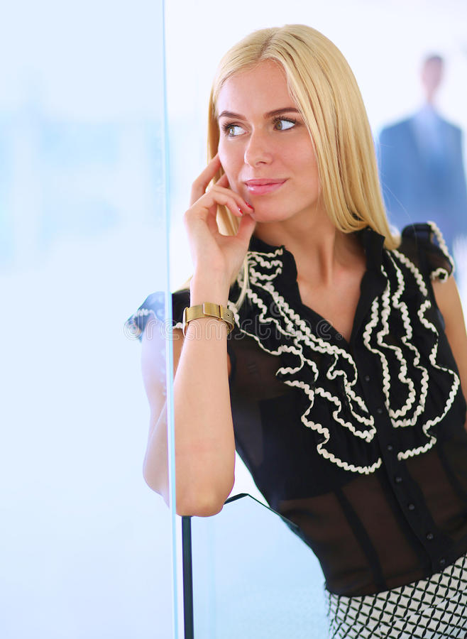 Business woman standing in foreground in office royalty free stock image
