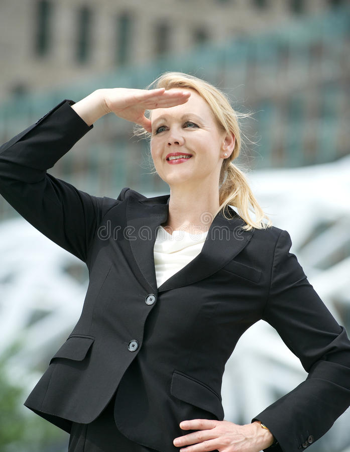 Business woman standing with hand salute outdoors. Portrait of a business woman standing with a hand salute outdoors stock photo