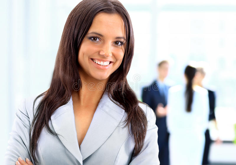 Business woman standing with her staff in background at office. Successful business woman standing with her staff in background at office stock image