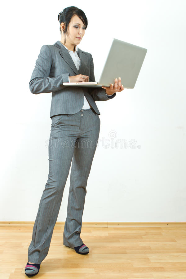 Business woman standing holding laptop stock photography