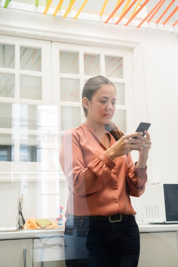 Business woman standing in a kitchen texting. Business woman standing in a kitchen, wearing an orange shirt and black trousers as she texts from a cell phone royalty free stock photography