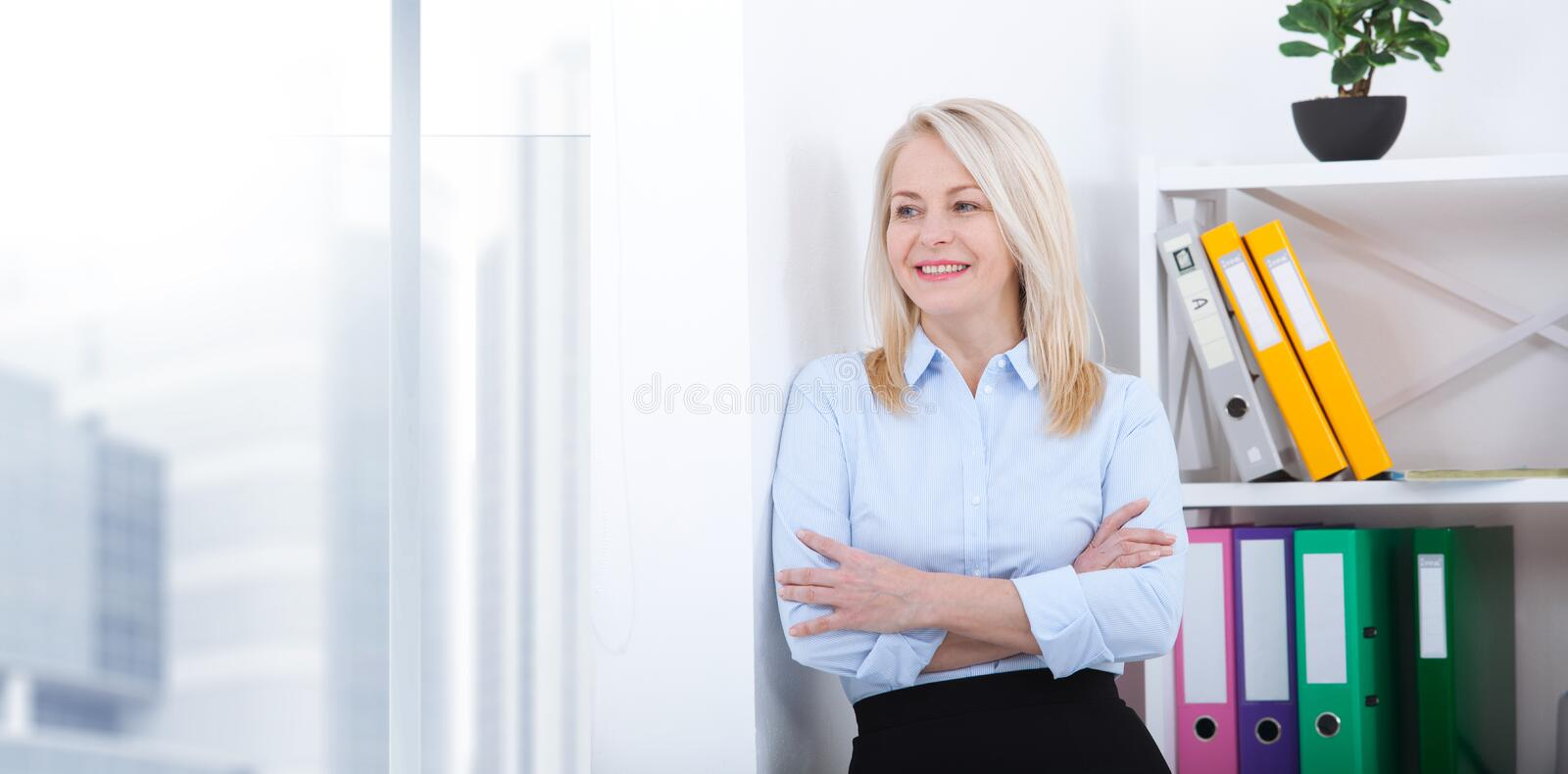 Business woman standing near the wall looking out the window thinking over the strategy. royalty free stock photos