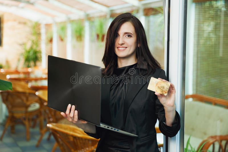 Business woman standing in restaurant with laptop and showing cr. Edit card royalty free stock images