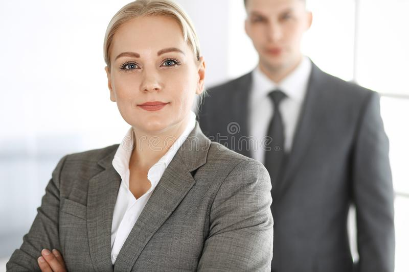 Business woman standing straight with colleague businessman in office, headshot. Success and corporate partnership stock photo