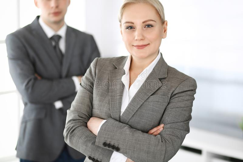 Business woman standing straight with colleague businessman in office, headshot. Success and corporate partnership royalty free stock photography