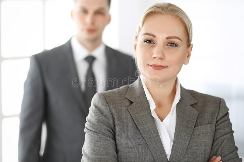 Business woman standing straight with colleague businessman in office, headshot. Success and corporate partnership royalty free stock photos
