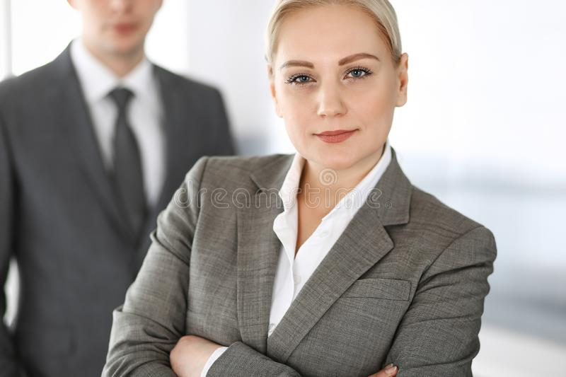 Business woman standing straight with colleague businessman in office, headshot. Success and corporate partnership royalty free stock images