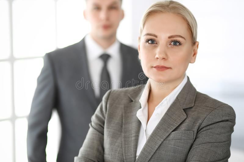 Business woman standing straight with colleague businessman in office, headshot. Success and corporate partnership royalty free stock photo