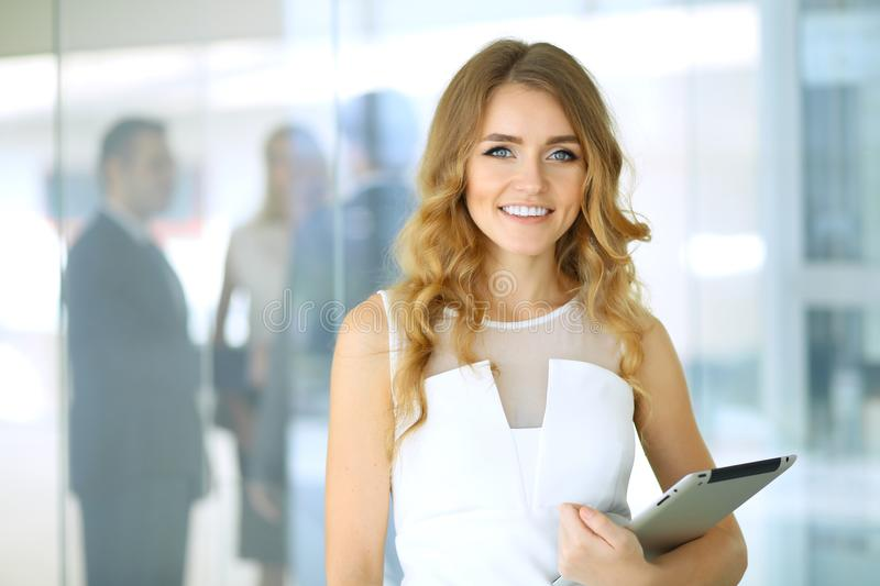 Business woman standing straight and smilling in office royalty free stock photo