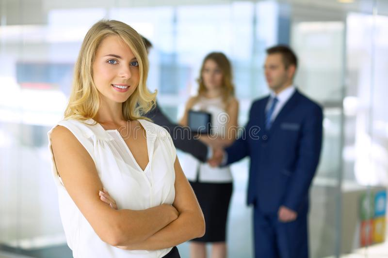 Business woman standing straight and smilling in office stock photo