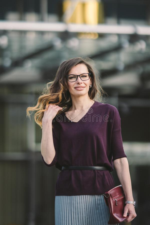 Business woman standing on street against office building. City business woman working. Portrait business woman smiling stock photo