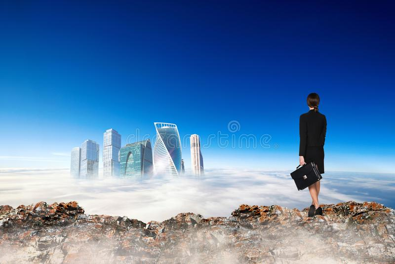 Business woman stands on the edge of mountain and looking on city. stock photo