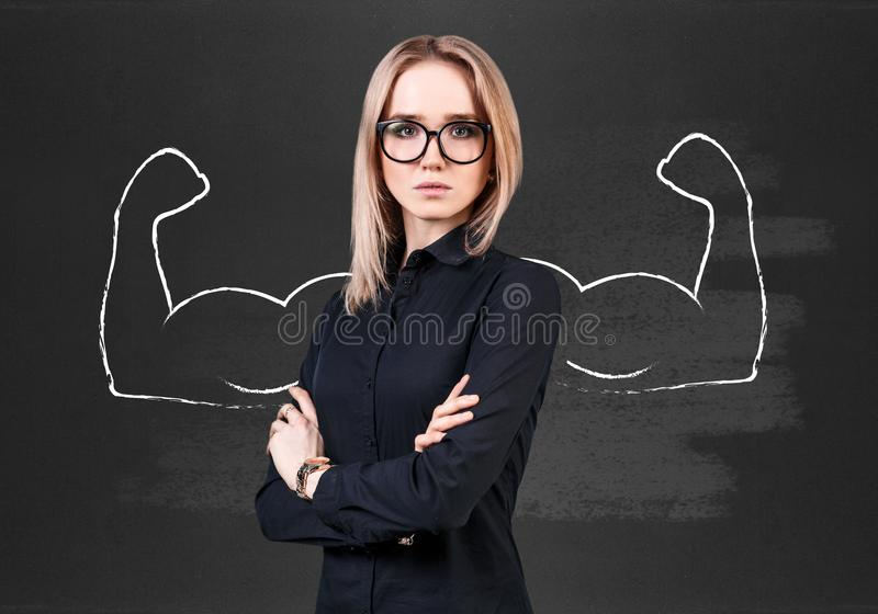 Business woman with drawn powerful hands. Business woman stands over chalkboard with drawn powerful hands stock photo
