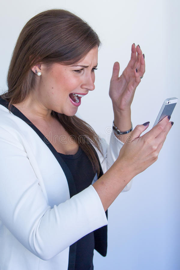 Business woman staring furiously on her cellphone. Young pretty business woman staring furiously on her cellphone royalty free stock photos