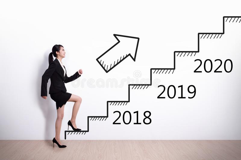 Woman success in new year. Business woman stepping up on stairs to gain her success in 2018 new year royalty free stock image