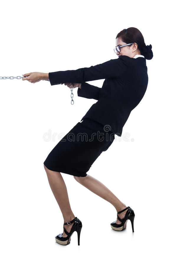 Business-woman-strength-pulling-chain. A businesswoman is trying to pull the chain and taking control with her strength royalty free stock image
