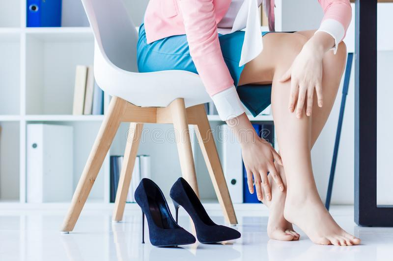 Tired beauty legs of confident business woman. Business woman in strict colorful clothes sitting in chair, hold legs has pain varicose veins symptom, arthritis royalty free stock photo