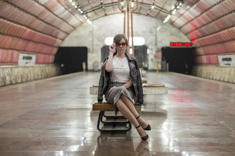 Business woman at subway station. Beautiful girl in sunglasses and a jacket at the subway station. Fashionable and stylish girl. stock image