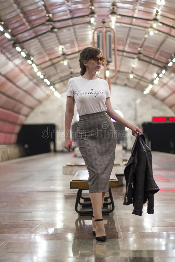 Business woman at subway station. Beautiful girl in sunglasses and a jacket at the subway station. Fashionable and stylish girl. S stock image