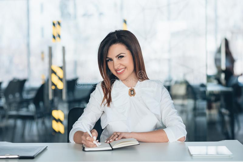 Business woman successful female team leader. Successful female team leader. Young brunette business woman siting at desk with pen and notebook, smiling royalty free stock photos