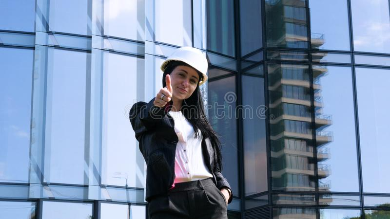 Business woman in suit and helment with crossed arms, looking at camera, smiling. Concept of: Skyscraper background, Communication stock image
