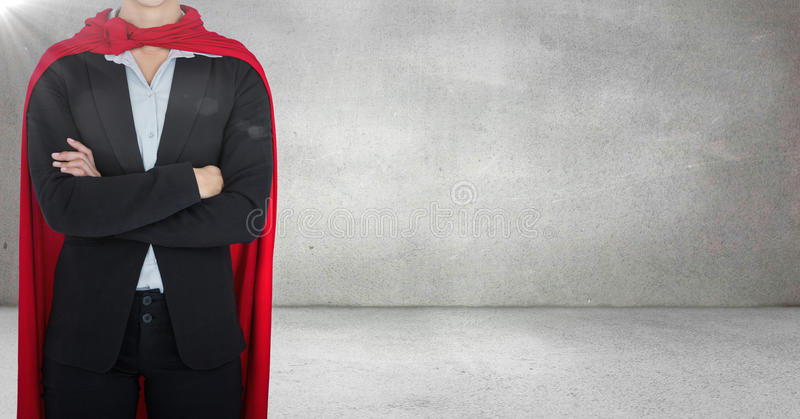 Business woman superhero with arms folded against grey wall with flare stock photo