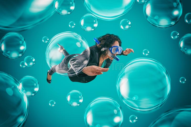 Woman swimming among air bubbles with mask and snorkel in a deep turquoise background. Business woman swims among transparent air bubbles stock photos