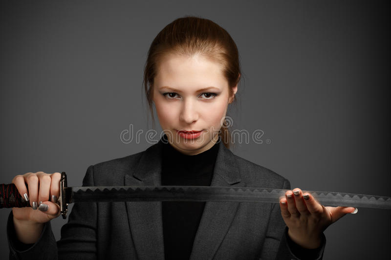 Business woman with a sword. Beautiful young business woman in dark jacket holding japan katana sword on grey background stock photos