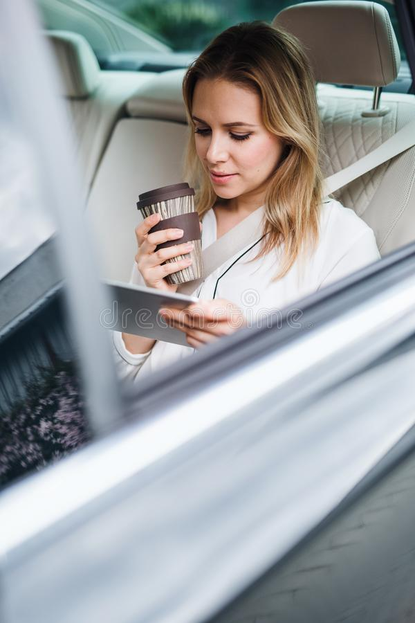 Business woman with tablet and coffee sitting on back seats in taxi car. stock photography