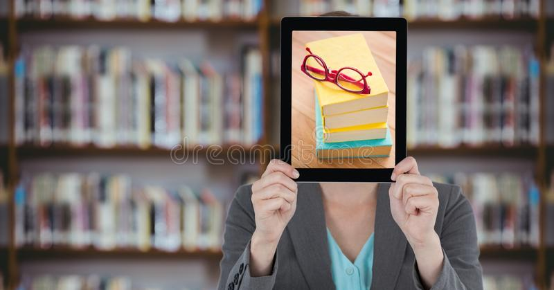 Business woman with tablet over her face with piles of books while standing at library royalty free stock photo